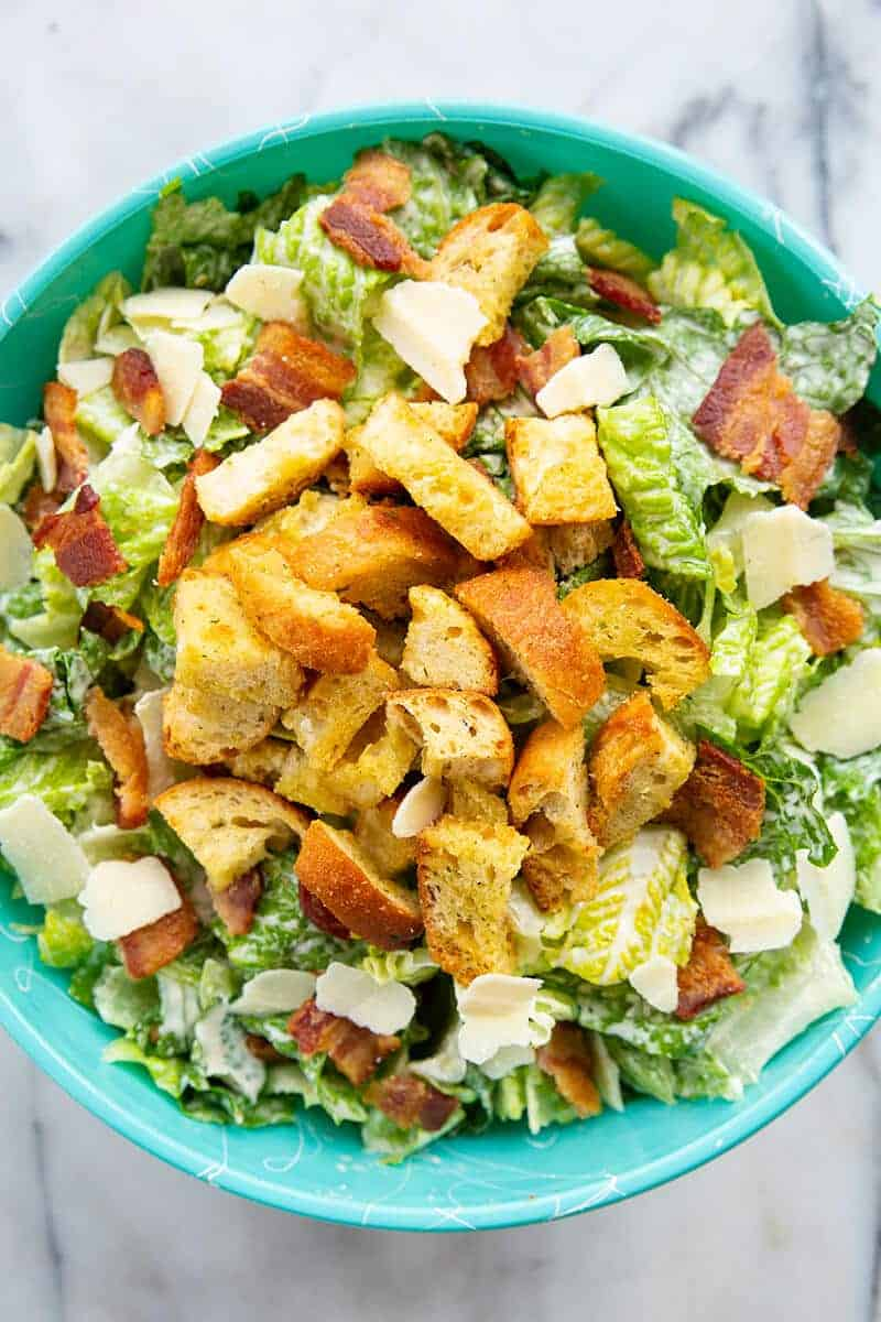 close up Caesar Salad in a jade blue bowl topped with bacon, HOMEMADE CROUTONS and Parmesan