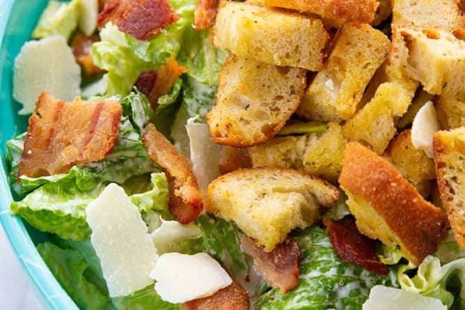Caesar Salad in a jade blue bowl topped with bacon, HOMEMADE CROUTONS and Parmesan