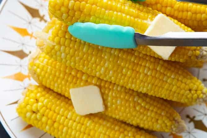getting a piece of hot buttered corn on the cob on a plate using kitchen tongs