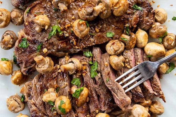 close up of fork holding slice of Cooked New York Strip Steak with Fried Garlic Mushrooms in a white plate