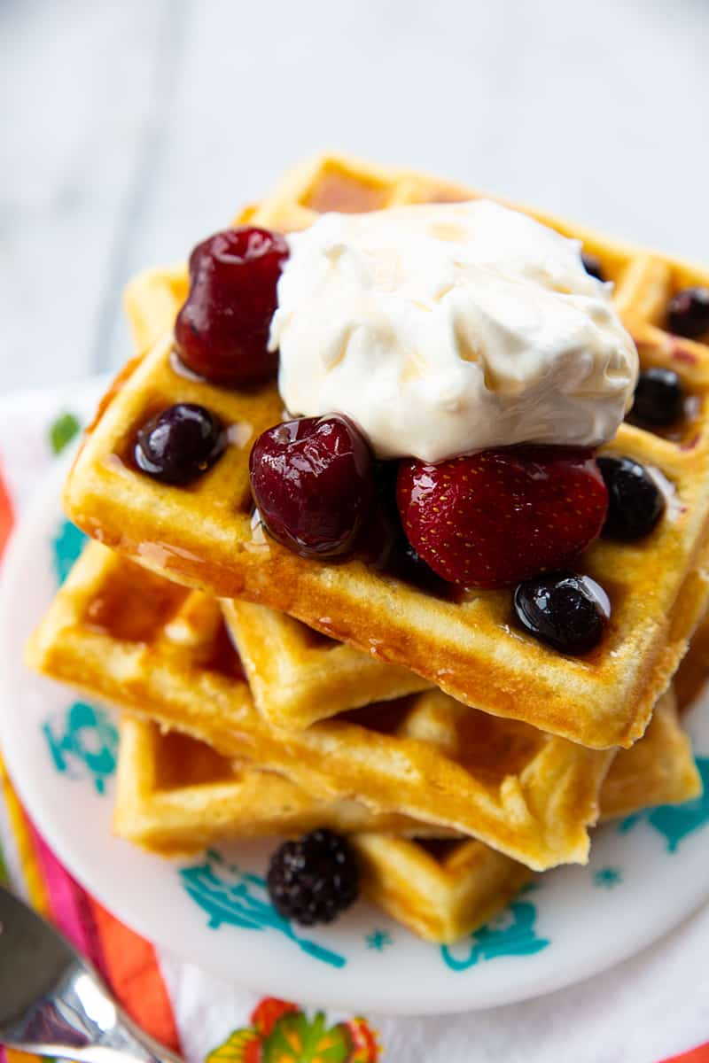 close up stack of Homemade Belgian Waffles topped with some berries and Whipped Cream