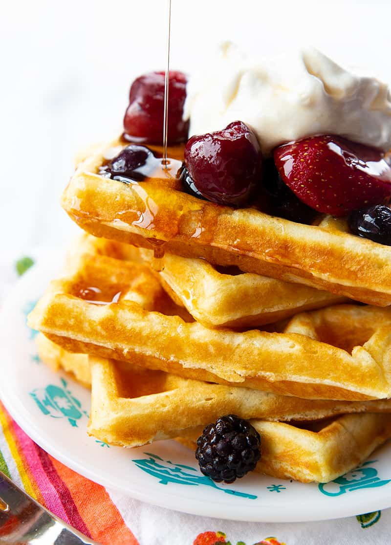 adding syrup to a stack of Homemade Belgian Waffles topped with some berries and Whipped Cream