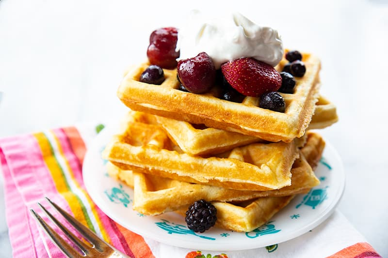 a plate with a stack of Homemade Belgian Waffles topped with some berries and Whipped Cream