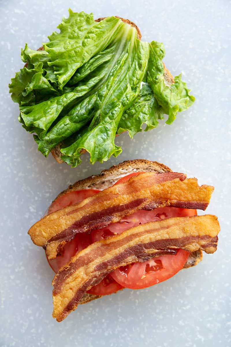BLT Sandwich ingredients - bread toast, strips of bacon, slices of tomatoes and lettuce leaf