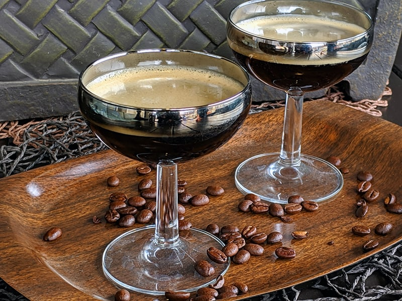 close up Two coupes on a wood serving tray with coffee beans scattered upon it.