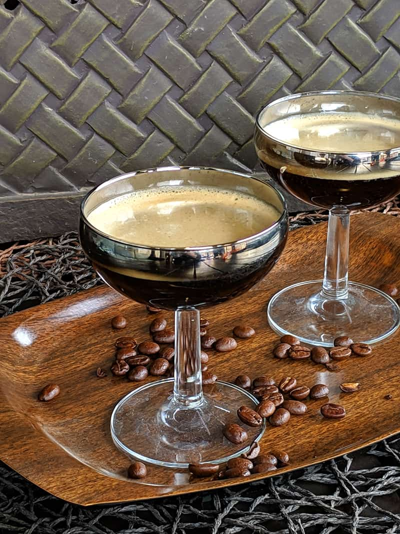 Two coupes on a wood serving tray with coffee beans scattered upon it.