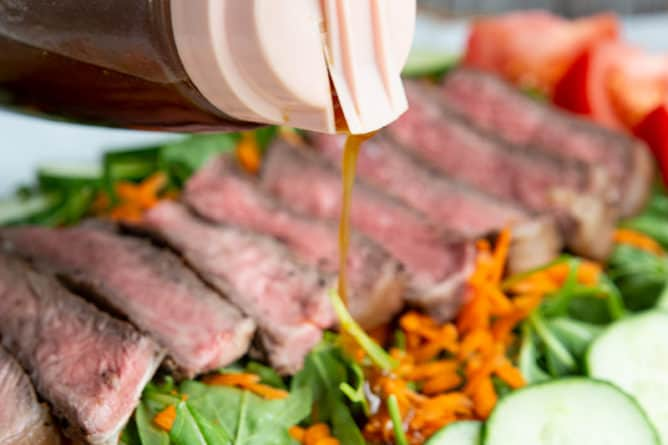 close up pouring Homemade Asian Salad Dressing to steak salad