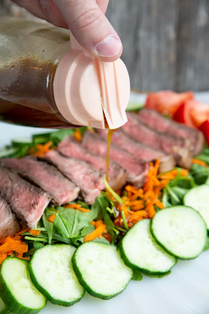 Asian Sesame Grilled Steak Salad in a white serving plate, drizzled with salad dressing