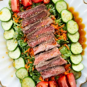 close up Asian Sesame Grilled Steak Salad in a white serving plate, drizzled with salad dressing and sprinkled with sesame seeds