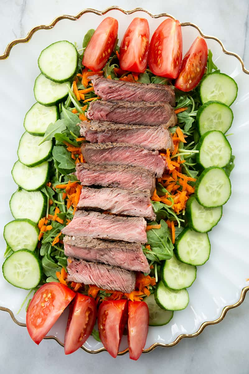 Asian Sesame Grilled Steak Salad in a white serving plate