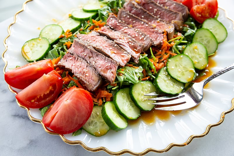Asian Sesame Grilled Steak Salad in a white serving plate, drizzled with salad dressing and sprinkled with sesame seeds