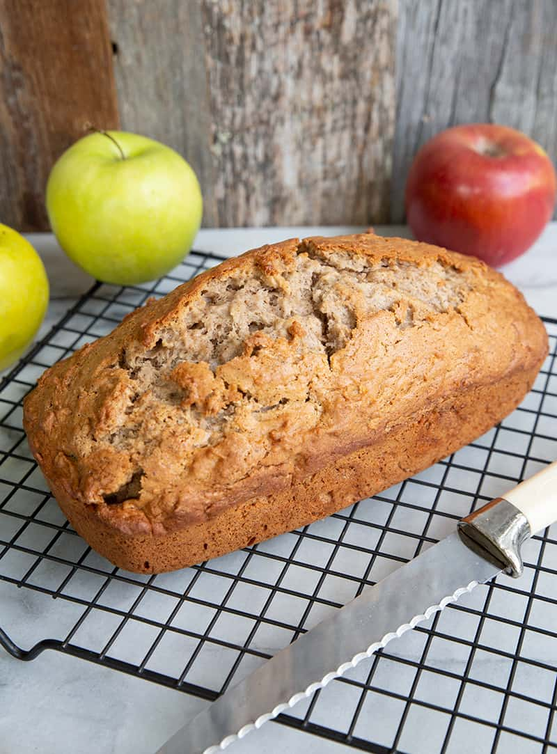 close up bread knife and Cinnamon Spice Apple Bread in a wire rack, apples on background