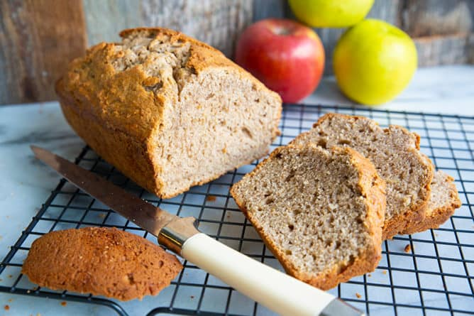 close up bread knife and sliced Cinnamon Spice Apple Bread in a wire rack, apples on background