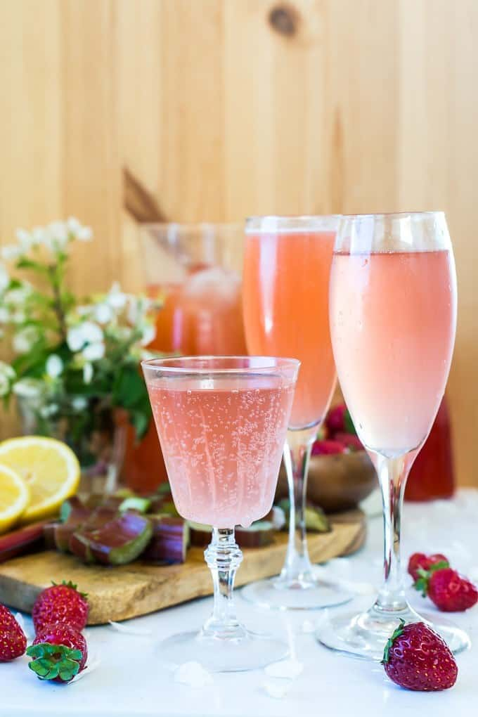 glasses of Strawberry Rhubarb Gin Fizz, slices of lemon and fresh strawberries on background