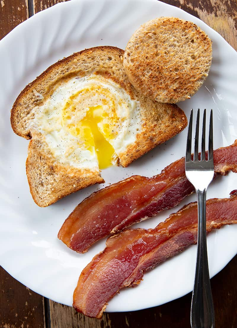 close up of Eggs in a Basket on a white plate with bacon