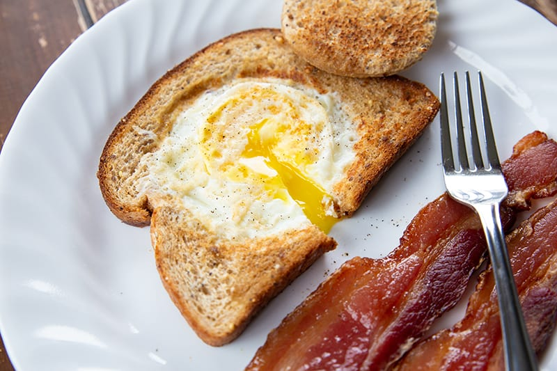 white plate with strips of bacon and Eggs in a Basket - crispy toasted bread with a gooey egg centre