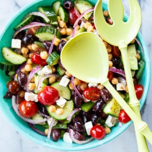 a bowl of Mediterranean Chickpea Salad with a large serving spoon and fork