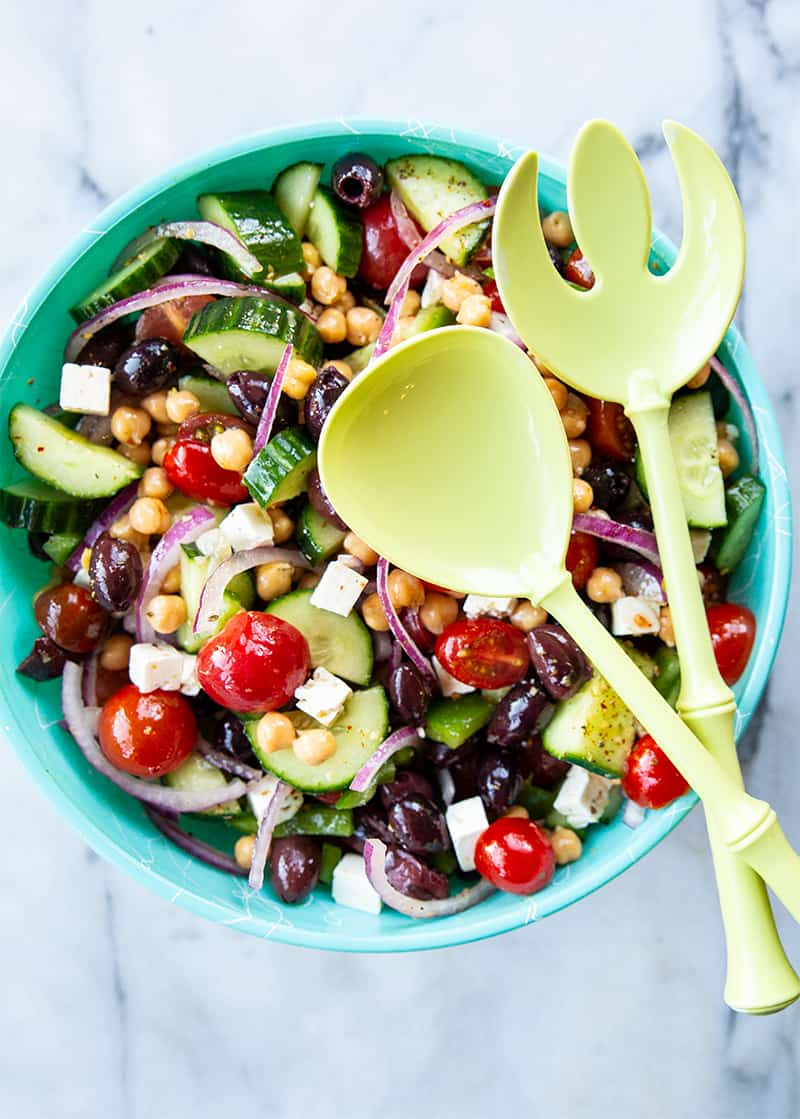 a bowl of Mediterranean Chickpea Salad with a large serving spoon and fork on a marble background