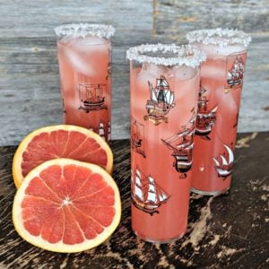 Three Salty Dog Cocktails on a table with sliced grapefruit served in Pirate Ship glasses