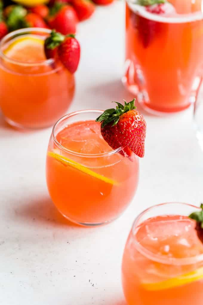 glasses of Strawberry Rhubarb Gin Fizz with a slice of lemon and fresh strawberry