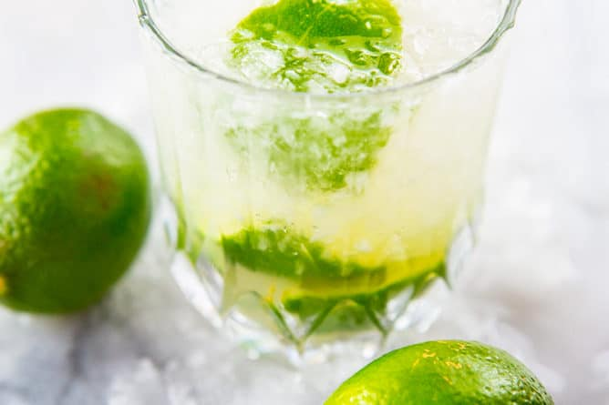 close up glass of Caipirinha with crushed ice, garnish with lime