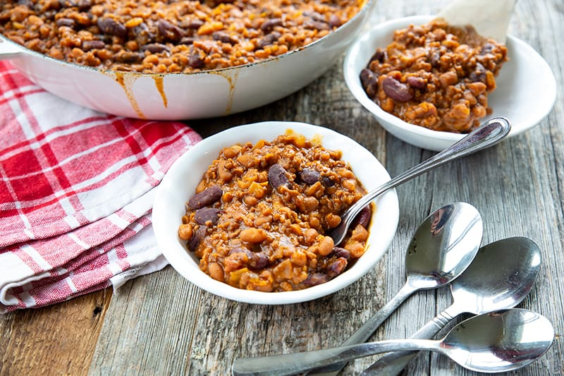 some serving of Cowboy Beans in white small plates, red checkered kitchen cloth and spoons on the side