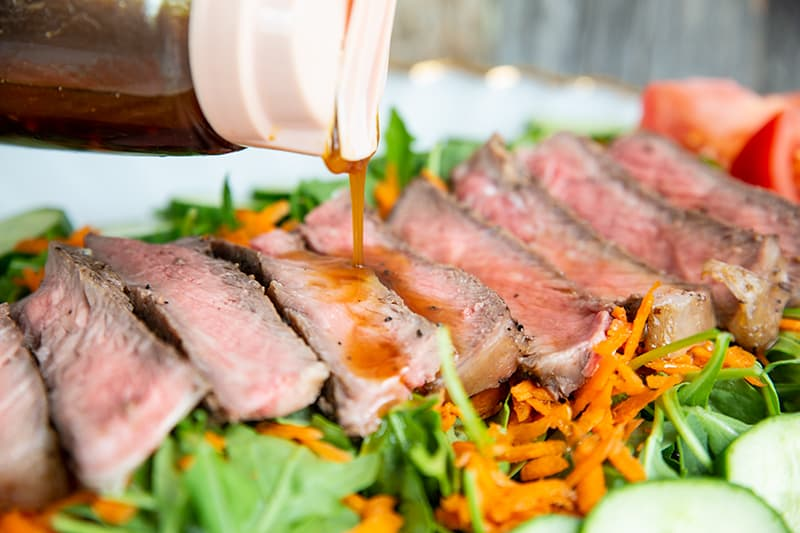 pouring Homemade Asian Salad Dressing to steak salad