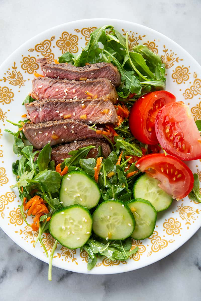 white floral designed plate with steak salad