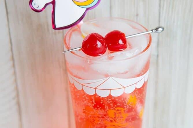 Shirley Temple drink with unicorn straw and garnish with maraschino cherries