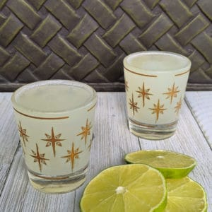 Two shot glasses with alcohol on a board with lime slices