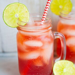 close up Madras Vodka Drink with red white straws on mason jars with handle, garnish with lime slices