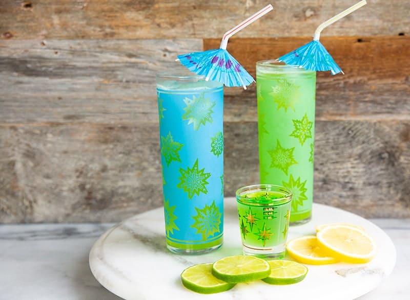glasses of Midori Sour Cocktail garnish with Umbrella, Lemon Slice and Lime Slice
