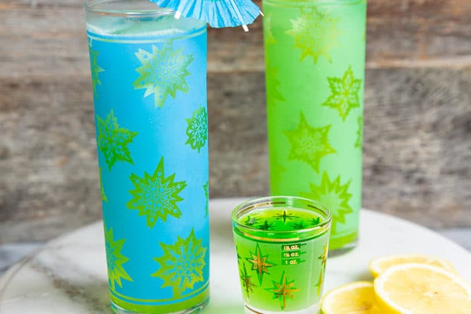 Two Tom Collins glasses filled with Midori Sour on marble with a shot glass and lemon and lime slices.