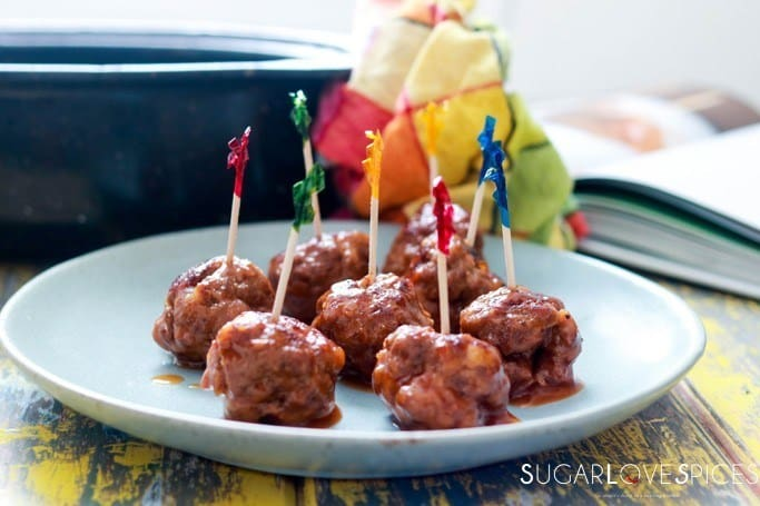 a plate with some Sweet and Sour Meatballs with toothpicks