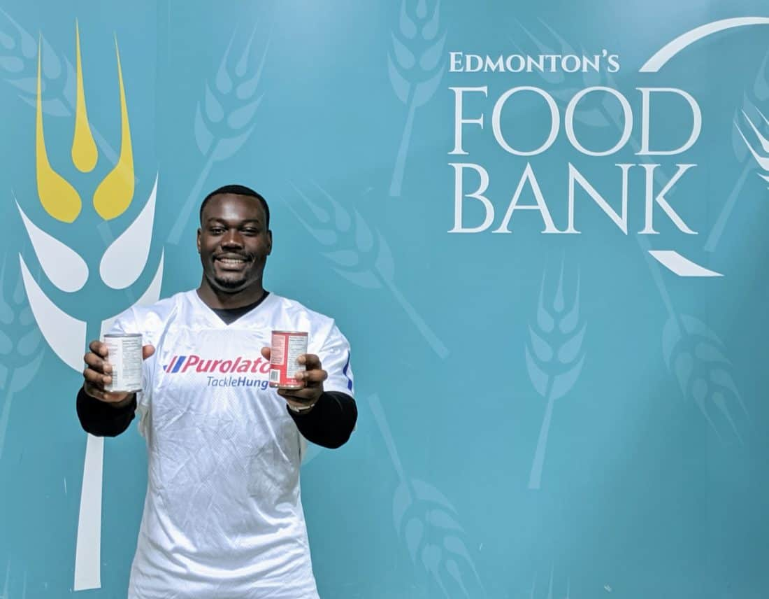 Kwaku holding 2 cans, Edmonton's Food Bank wallpaper on his background