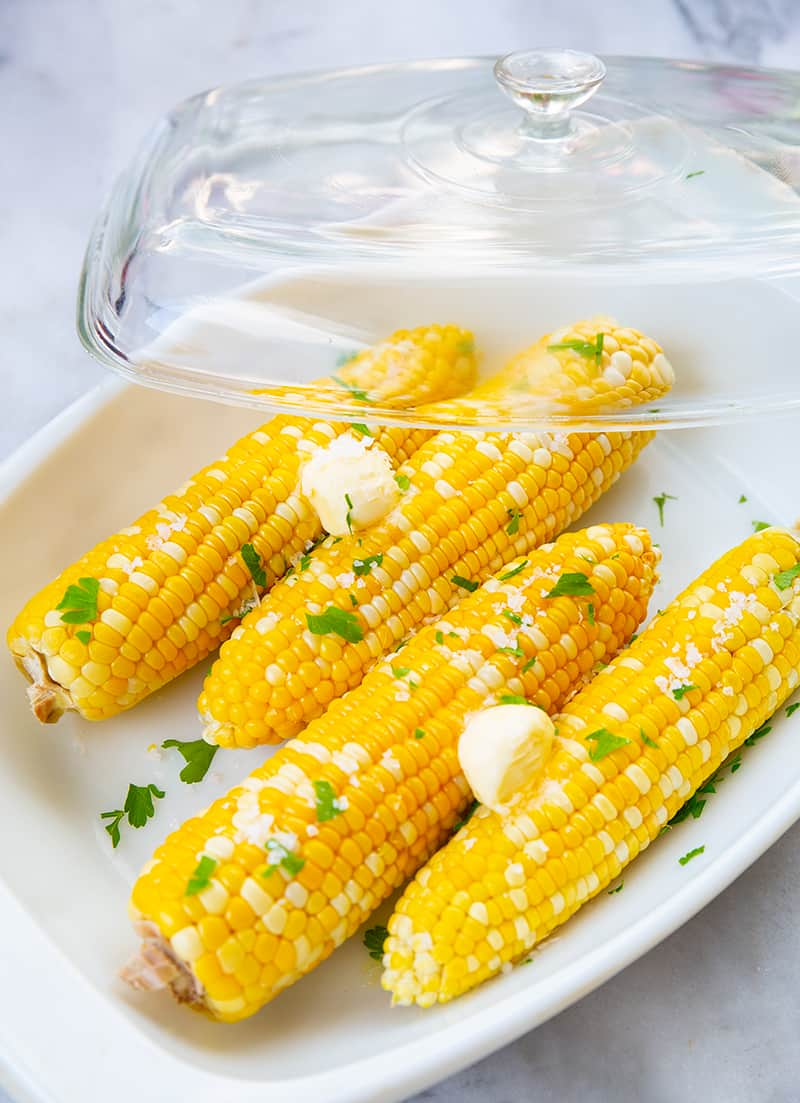 close up Microwaved Corn on the Cob with butter in a casserole dish