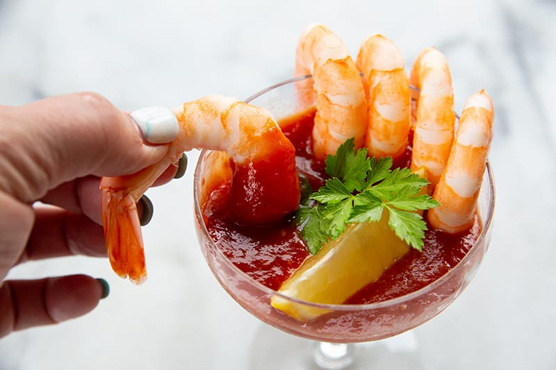 5 cocktail shrimp around a serving glass with Cocktail Sauce garnish with a slice of lemon and parsley leaves