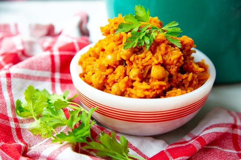 red checkered tablecloth underneath a bowl of Jollof rice with chickpeas garnish with parsley