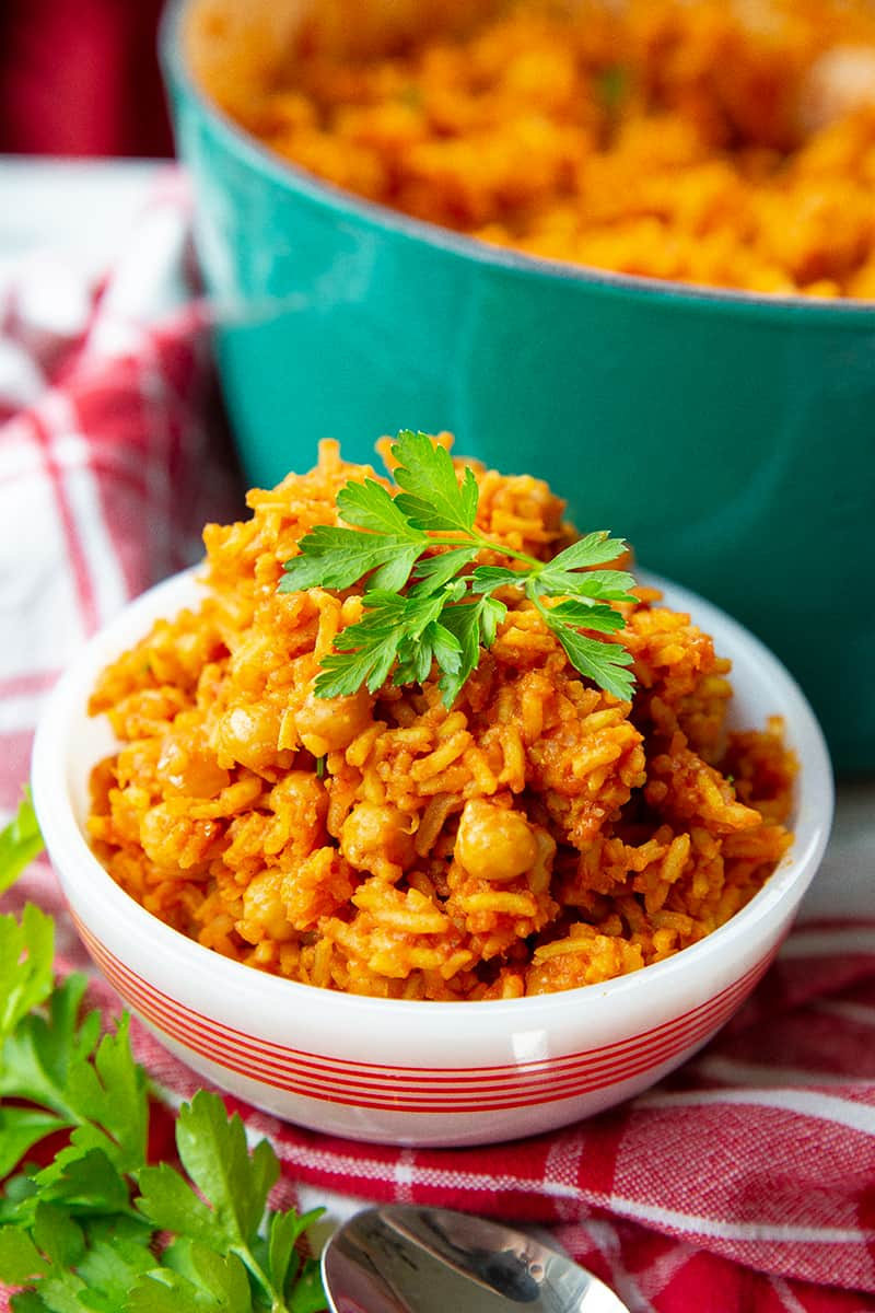close up red checkered tablecloth underneath a bowl of Jollof rice with chickpeas garnish with parsley