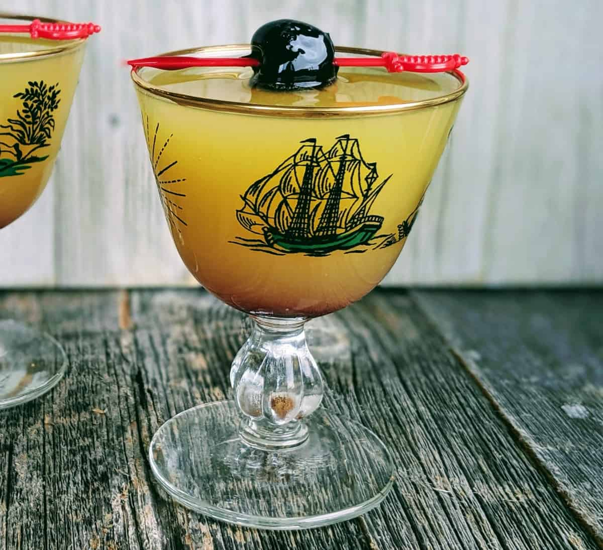 close up Monkey Gland Cocktail in a Pirate Coupe garnished with a Luxardo Maraschino Cherry