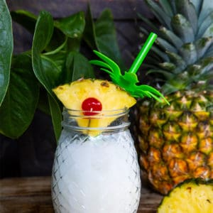 close up Pina Colada in a pineapple jar garnish with a pineapple slice. Fresh pineapple on background.