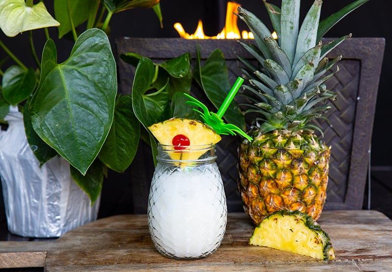 Pina Colada in a pineapple jar garnish with a pineapple slice. Fresh pineapple on background.
