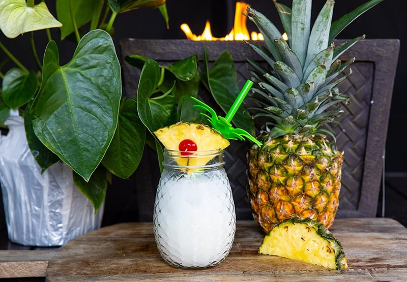 pina colada cocktail using a pineapple wedge as a garnish, with a large whole pineapple beside it