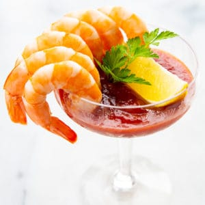 6 cocktail shrimp around a serving glass with Cocktail Sauce garnish with a slice of lemon and parsley leaves