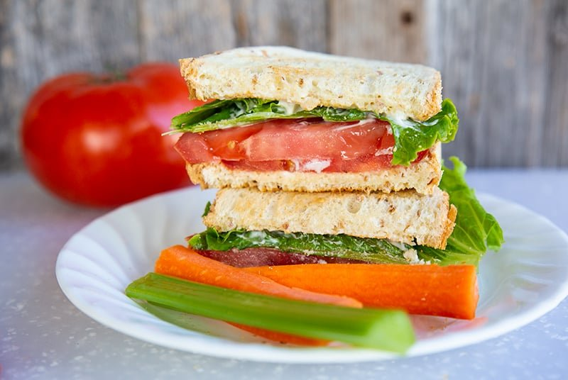Classic Toasted Tomato Sandwich in a white plate. A large tomato on the background