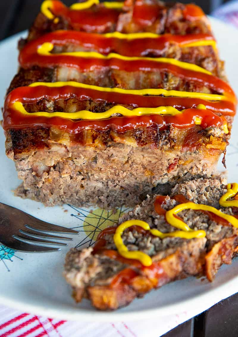 a plate of Bacon Cheeseburger Meatloaf slice up and topped with cheese, mustard and ketchup