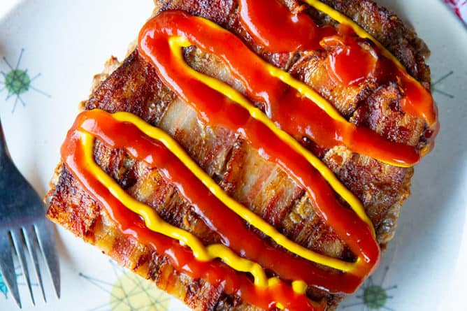slice up Bacon Cheeseburger Meatloaf topped with cheese, mustard and ketchup in a white plate with fork