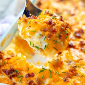 close up spoonful of Baked Cheesy Potato Casserole topped with chives and bacon