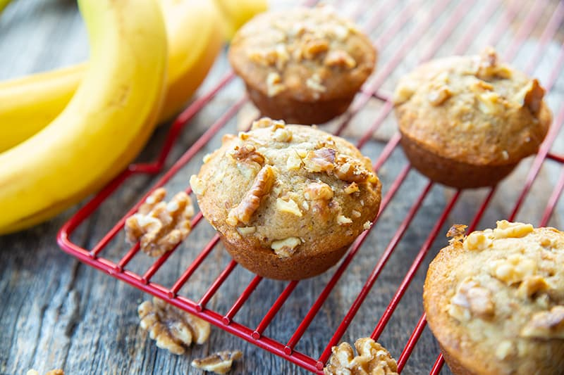 Banana Nut Muffins in red cooling rack, ripe bananas on its background