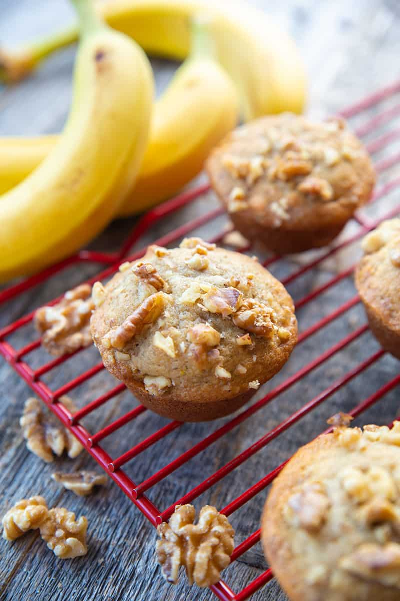 close up Banana Nut Muffins in red cooling rack, ripe bananas on its background